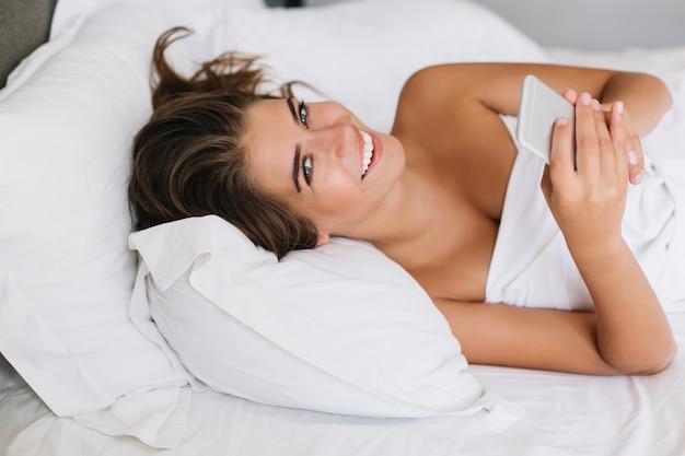 Portret atrakcyjna dziewczyna z telefonem na łóżku rano w nowoczesnym mieszkaniu.