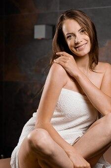 Portret atrakcyjna dziewczyna zawinięta w ręcznik po prysznicu.