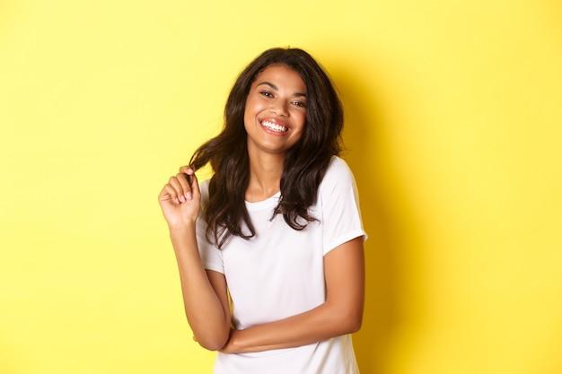 Portret atrakcyjna i pewna siebie afroamerykanka ubrana w białą koszulkę, uśmiechnięta szczęśliwa i bawiąca się włosami