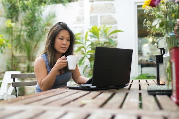 Portret atrakcyjna japonka za pomocą laptopa. piękna dziewczyna z brązowymi włosami robi zakupy lub rozmawia online, bawi się, ogląda film, pracuje jako freelancer. piję kawę