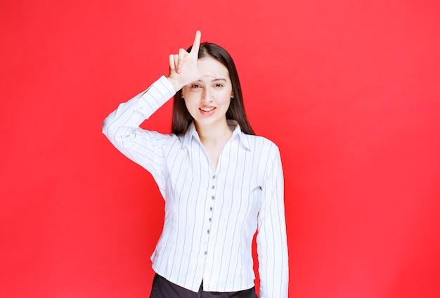 Portret atrakcyjna kobieta drwi z ludzi palcami na czole robi gest przegrany.