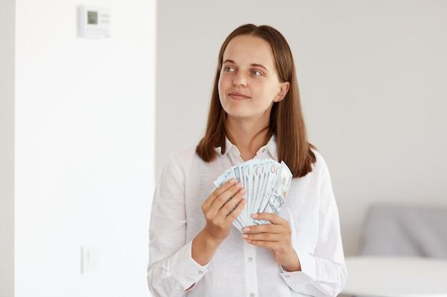 Portret atrakcyjna kobieta o ciemnych włosach, ubrana w białą koszulę w stylu casual, stojąca z banknotami dolarów w dłoniach, odwracająca wzrok z marzycielskim wyrazem twarzy, marząca o zakupach.