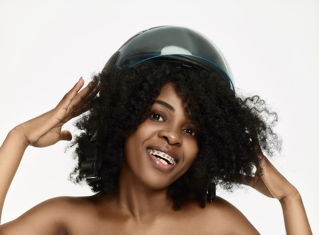 Portret atrakcyjna kobieta w kasku motocyklowym na ścianie białego studia