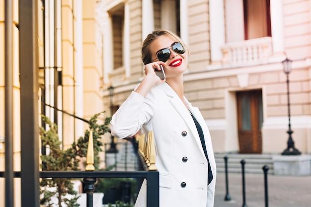 Portret atrakcyjna kobieta w okularach przeciwsłonecznych na ulicy. mówi przez telefon i uśmiecha się do kamery.