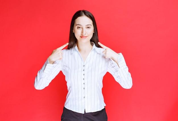 Portret atrakcyjna kobieta, wskazując na jej uśmiech na czerwonej ścianie.