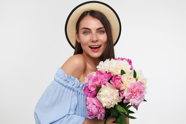 Portret atrakcyjna, ładnie wyglądająca dziewczyna z dużym uśmiechem i długimi brunetkami. w kapeluszu i niebieskiej sukience. trzymając bukiet kwiatów i oglądając na białym tle nad białą ścianą