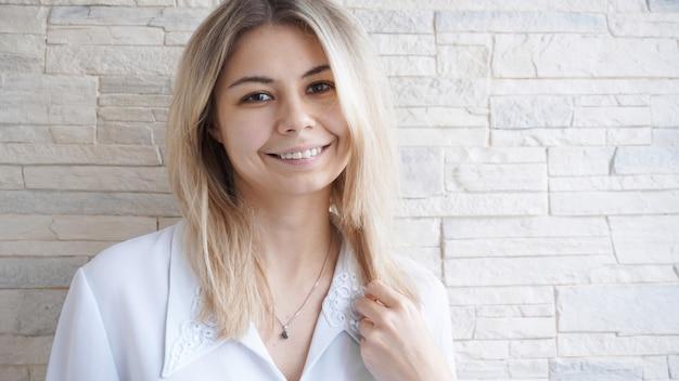 Portret atrakcyjna młoda bizneswoman europejska na ceglany mur. koncepcja sukcesu