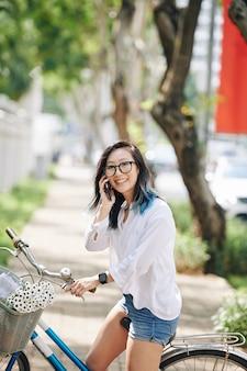 Portret atrakcyjna młoda chinka siedzi na rowerze i rozmawia telefon z przyjacielem