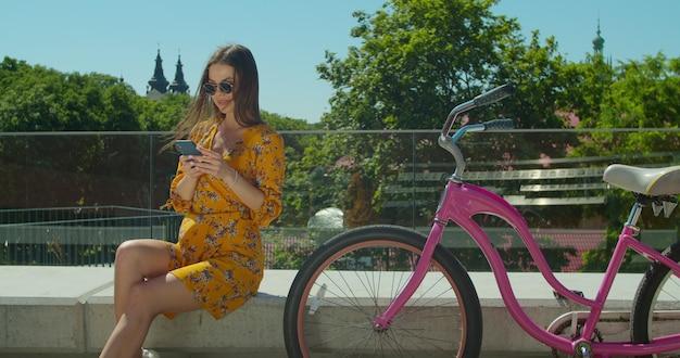 Portret atrakcyjna młoda dziewczyna brunetka na rowerze używany smartfon siedzący na ławce w parku.