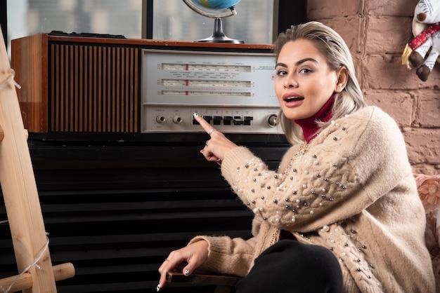 Portret atrakcyjna młoda dziewczyna obracając gramofonu siedząc i odwracając wzrok