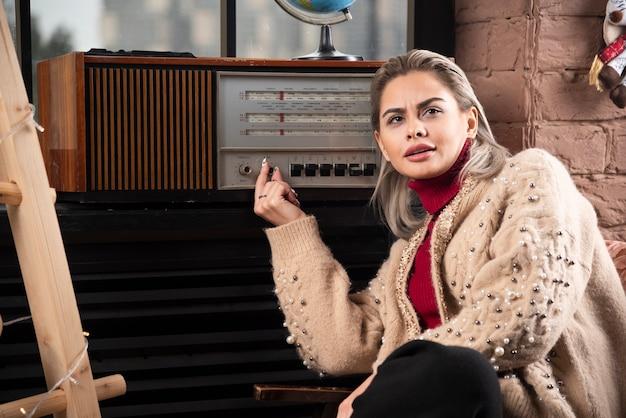 Portret atrakcyjna młoda dziewczyna obracając gramofonu siedząc