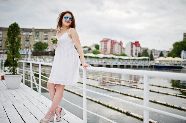 Portret atrakcyjna młoda kobieta pozuje z jej koktajlem na brzeg jeziora jest ubranym okulary przeciwsłonecznych.