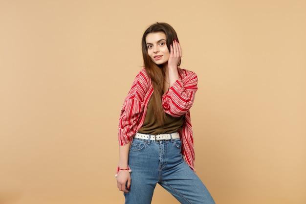 Portret atrakcyjna młoda kobieta w ubraniach casual, kładąc rękę na głowie, patrząc na kamerę na białym tle na pastelowym beżowym tle w studio. ludzie szczere emocje, koncepcja stylu życia. makieta miejsca na kopię.