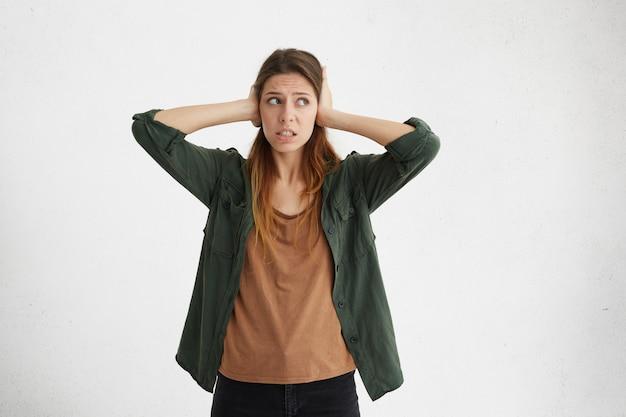 Portret atrakcyjna młoda kobieta w ubranie, obejmujące uszy rękami, nie chcąc słyszeć głośnego dźwięku. ładna suczka pragnąca spokoju i ciszy próbująca uchronić się przed hałasem