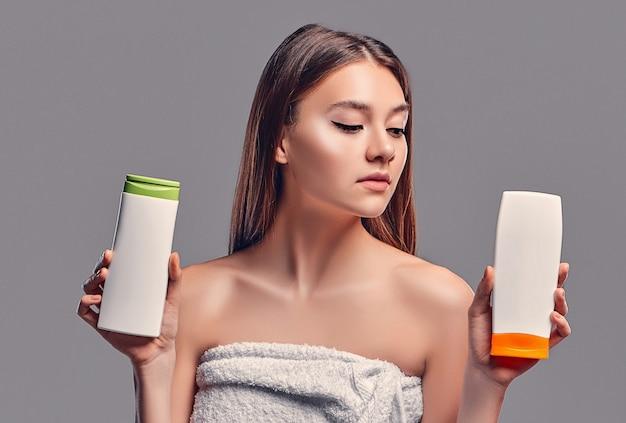 Portret atrakcyjna młoda kobieta z dwoma szamponami na szarym tle. dokonywanie wyboru. pielęgnacja kobiet