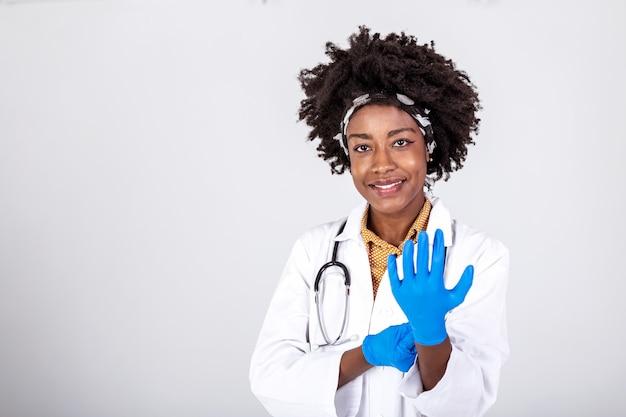 Portret atrakcyjna młoda lekarka w białym fartuchu zakładanie rękawiczek medycznych.