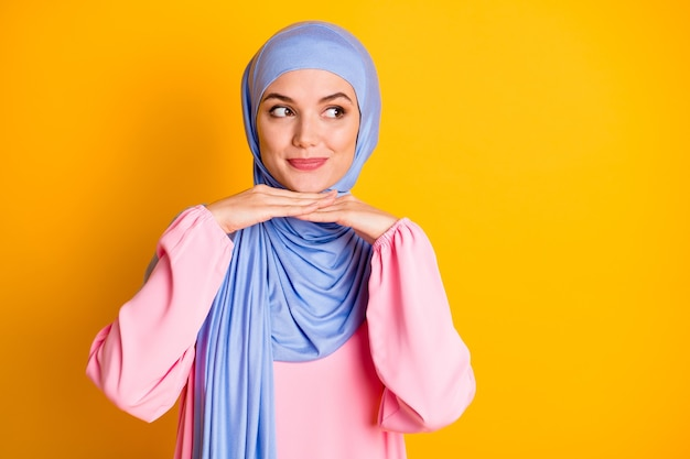 Portret atrakcyjna, nieśmiała, skromna, wesoła muzułmańska dama nosząca hidżab pozowanie patrząc na bok na białym tle nad jasnym żółtym kolorem tła