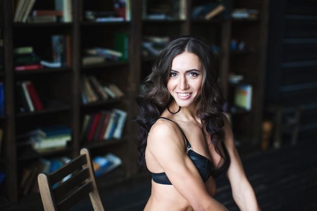 Portret atrakcyjna sport kobieta na tle książek.