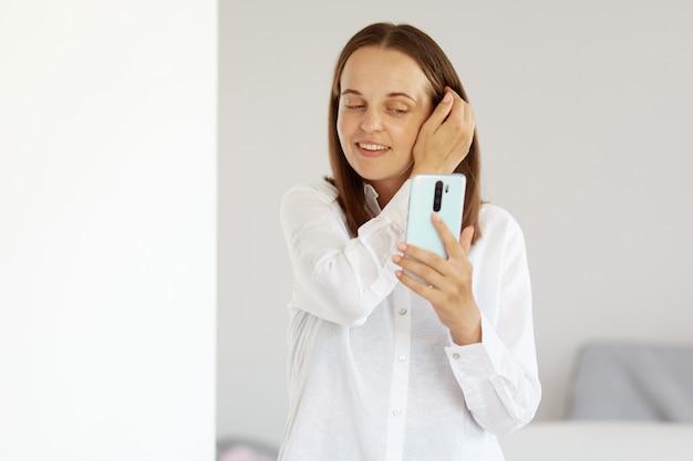 Portret atrakcyjna szczęśliwa kobieta ubrana w białą koszulę w stylu casual, trzymająca telefon komórkowy w rękach, biorąca selfie, patrząca na wyświetlacz smartfona, pozowanie w jasnym pokoju w domu.