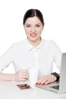 Portret atrakcyjna szczęśliwa udana bizneswoman brunetka z makijażem w białej koszuli siedzącej, patrząc na kamery z toothy uśmiechem i szczęściem. kryty strzał studio, odizolowane w białym tle.