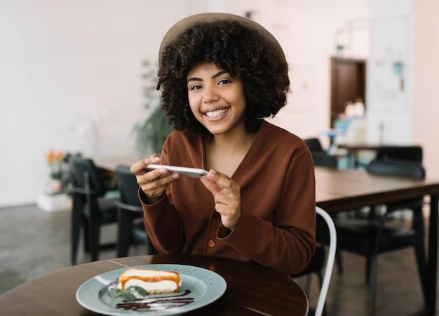 Portret atrakcyjna uśmiechnięta amerykanin afrykańskiego pochodzenia kobieta używa smartphone i bierze mobilnego fotografii cheesecake na talerzu. pozytywny bloger kulinarny, który publikuje posty w sieciach społecznościowych