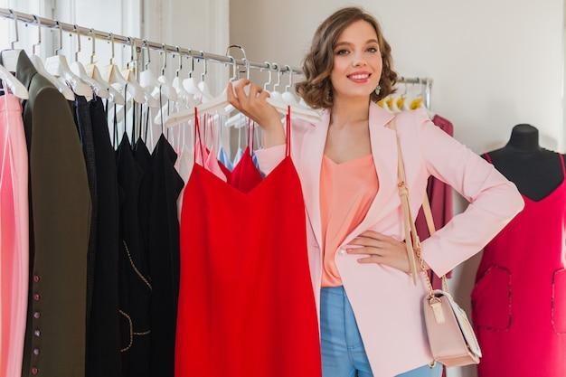 Portret atrakcyjna uśmiechnięta kobieta trzymając spódnicę dżinsową na wieszaku w sklepie odzieżowym