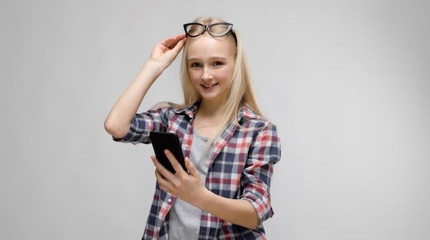 Portret atrakcyjna uśmiechnięta słodka urocza blondynka nastolatka w kratkę ubrania