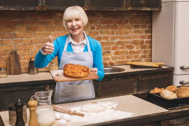 Portret atrakcyjna uśmiechnięta szczęśliwa starsza starzejąca się kobieta gotuje na kuchni. babcia co smaczne pieczenia. kciuki w górę.
