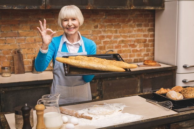 Portret atrakcyjna uśmiechnięta szczęśliwa starsza starzejąca się kobieta gotuje na kuchni. babcia co smaczne pieczenia. ok znak.