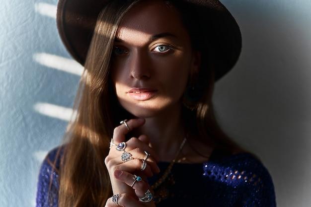 Portret atrakcyjna zmysłowa elegancka brunetki kobieta w kapeluszu jest ubranym biżuterię z nakładkami ocienia na oczach
