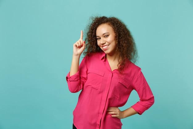 Portret atrakcyjne dziewczyny afryki w różowe ubrania dorywczo wskazując palcem wskazującym się na białym tle na tle niebieskiej ściany turkus w studio. koncepcja życia szczere emocje ludzi. makieta miejsca na kopię.