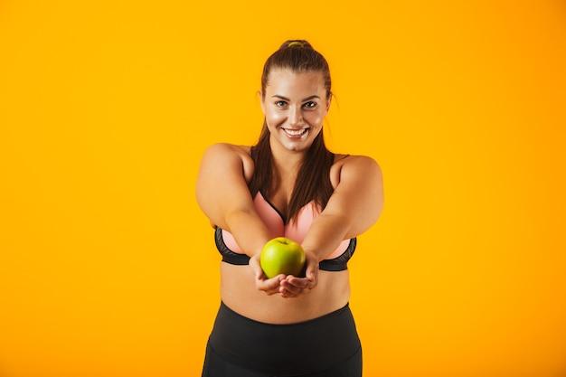 Portret atrakcyjne kobiety grube w stanik sportowy gospodarstwa jabłko, odizolowane na żółtym tle