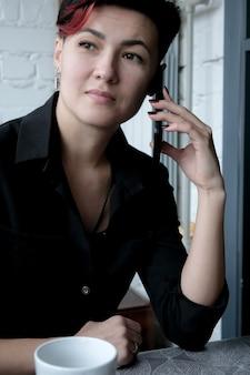 Portret atrakcyjne, młode, dorosłe kobiety rozmawia przez telefon komórkowy z kubkiem gorącego napoju