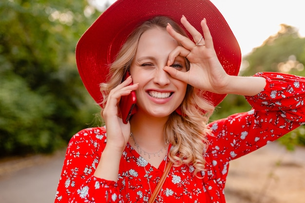 Portret atrakcyjne stylowe blond uśmiechnięta kobieta w słomkowym czerwonym kapeluszu i bluzce moda lato strój rozmawia telefon pozytywne emocje gestu