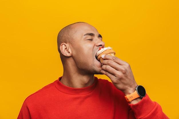 Portret atrakcyjnego dorywczo młodego afrykańskiego mężczyzny stojącego nad żółtą ścianą, jedzącego babeczkę