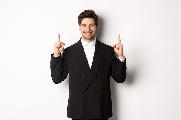 Portret atrakcyjnego kaukaskiego mężczyzny w stylowym czarnym garniturze, wskazując palcami w górę i uśmiechnięty, pokazujący bożonarodzeniową reklamę, stojący nad białym tłem.