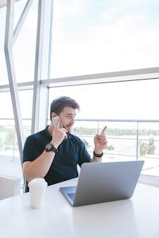 Portret atrakcyjnego mężczyzny siedzącego w kawiarni przy filiżance kawy i laptopie, rozmawia przez telefon i uśmiecha się