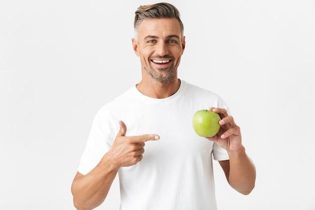Portret atrakcyjnego mężczyzny w wieku 30 lat, który ma włosie w casualowej koszulce pozuje i trzyma w ręku zielone jabłko na białym tle