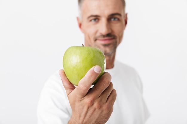 Portret atrakcyjnego mężczyzny w wieku 30 lat z włosiem pozuje i trzyma w ręku zielone jabłko na białym tle