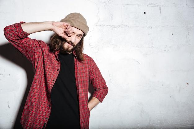 Portret atrakcyjnego młodego brodatego hipstera w kapeluszu ubranym w koszulę w klatce pozowanie na białym tle nad ścianą