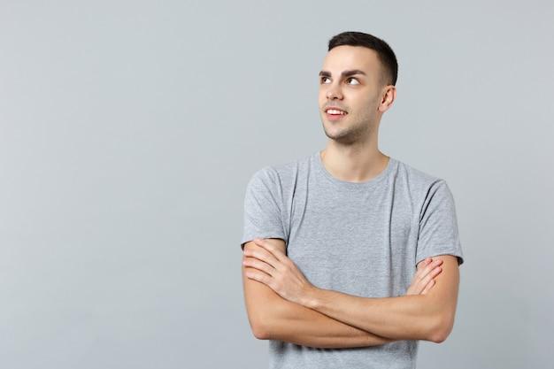 Portret atrakcyjnego młodego mężczyzny w zwykłych ubraniach, patrzącego na bok i trzymającego się za skrzyżowane ręce