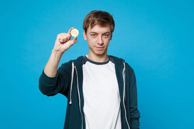 Portret atrakcyjnego młodzieńca w ubranie trzyma bitcoin, przyszła waluta na białym tle na niebieskiej ścianie. ludzie szczere emocje, koncepcja stylu życia.
