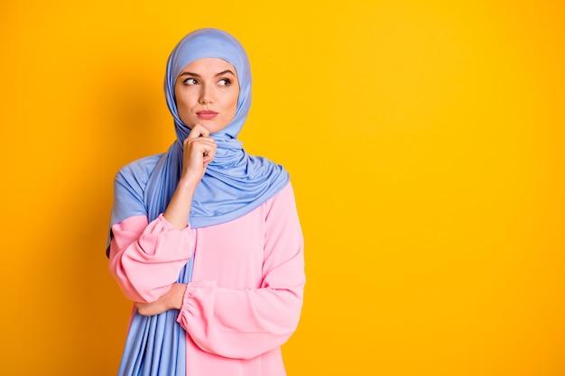 Portret atrakcyjnego myślącego, inteligentnego, mądrego muzułmanina noszącego hidżab myślącego na białym tle nad jasnożółtym kolorem tła