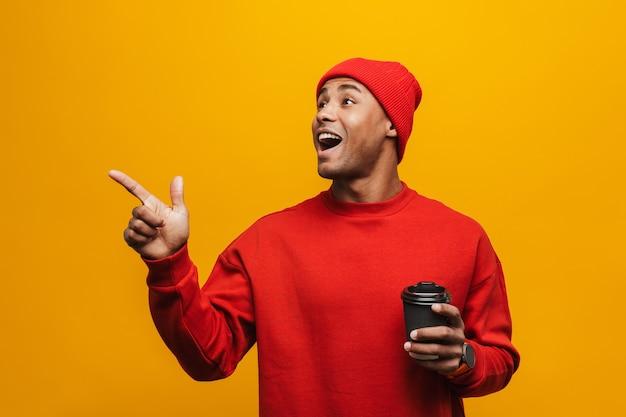 Portret atrakcyjnego, pewnego siebie, dorywczo młodego afrykańskiego mężczyzny stojącego nad żółtą ścianą, trzymającego filiżankę kawy na wynos, wskazującego palcem dalej