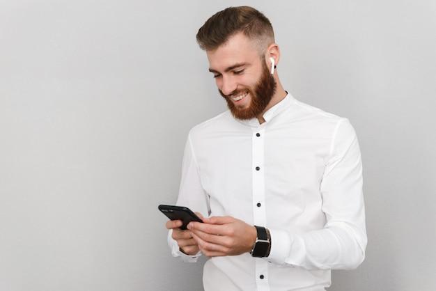 Portret atrakcyjnego, przystojnego, młodego biznesmena stojącego nad szarą ścianą, korzystającego z telefonu komórkowego