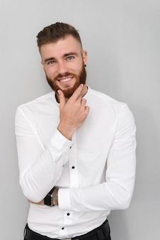 Portret atrakcyjnego, przystojnego, młodego biznesmena stojącego nad szarą ścianą, pozowanie