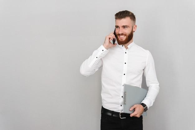 Portret atrakcyjnego, przystojnego młodego biznesmena stojącego nad szarą ścianą, rozmawiającego przez telefon komórkowy, trzymającego laptopa