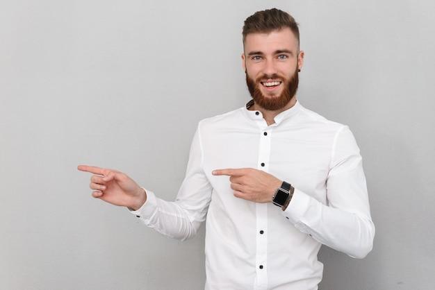 Portret atrakcyjnego, przystojnego, młodego biznesmena stojącego nad szarą ścianą, wskazującego palcem na miejsce kopiowania