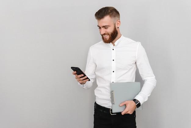Portret atrakcyjnego, przystojnego młodego biznesmena stojącego nad szarą ścianą, wysyłającego sms-y na telefon komórkowy, podczas gdy laptop holdinf