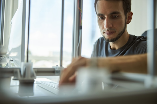 Portret atrakcyjnego skoncentrowanego brodatego poważnego młodego inżyniera płci męskiej pracującego w laboratorium badawczym